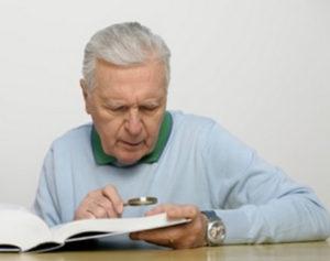 虫眼鏡片手に本を読んでいる人