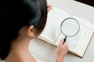 拡大鏡を使って本を読んでいる人